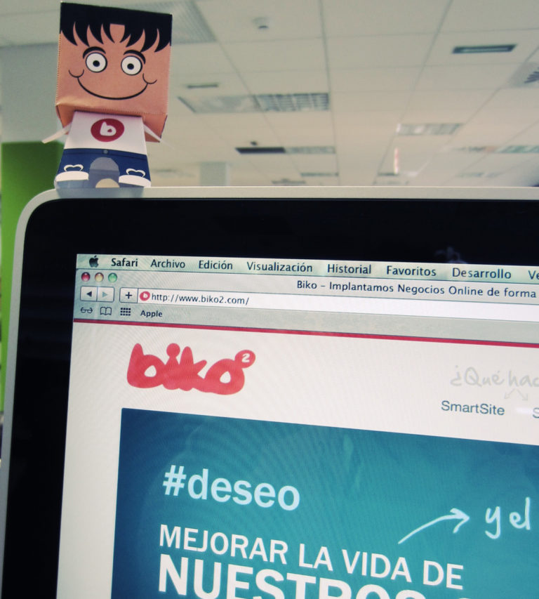 iMac mostrando la nueva web de Biko, con el consultor en papel encima