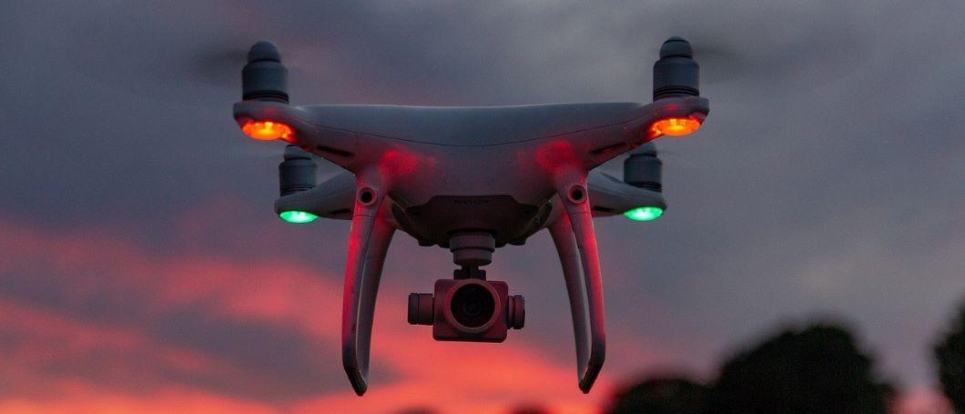 Dron de carreras con luces rojas y verdes suspendido en el aire